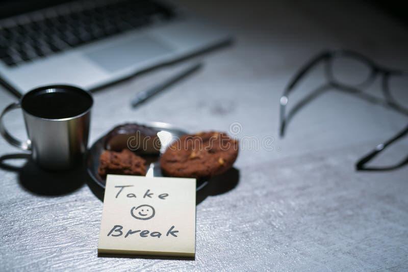 有膝上型计算机的办公室运转的书桌、笔和和玻璃和咖啡用曲奇饼和贴纸或者备忘录笔记 库存图片