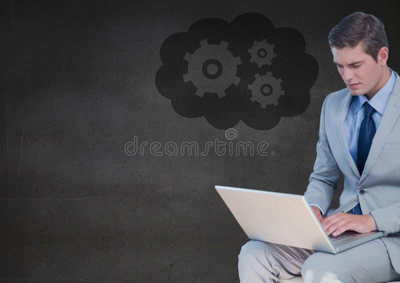 有膝上型计算机的商人对灰色墙壁和云彩与齿轮图表 图库摄影