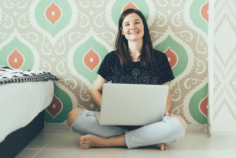有膝上型计算机的女孩自由职业者坐地板和笑 免版税库存图片
