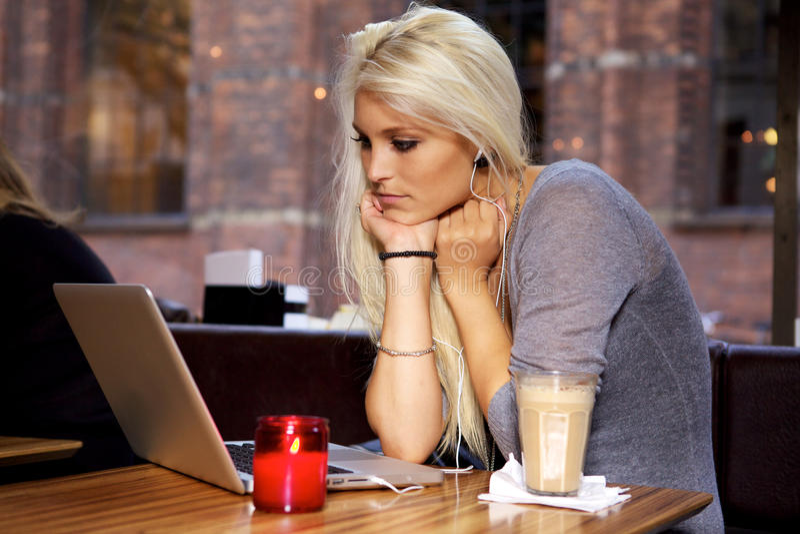 有膝上型计算机的妇女在咖啡馆