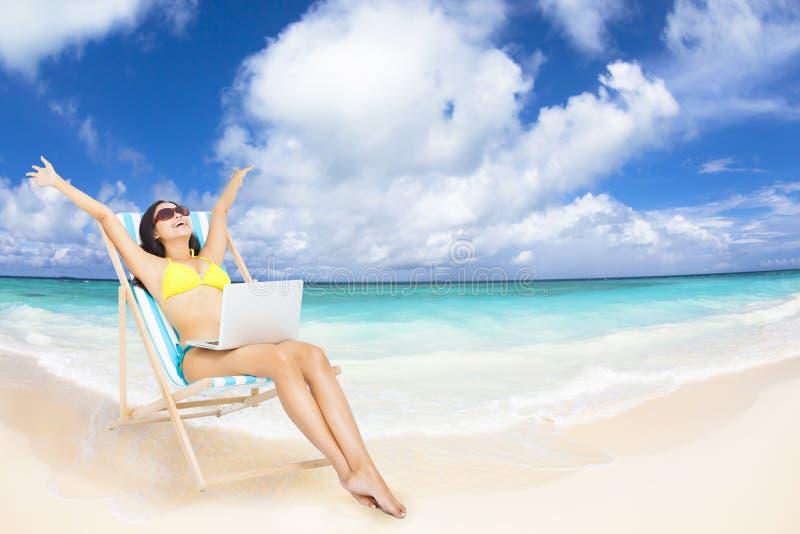 有膝上型计算机的妇女在热带海滩 库存照片