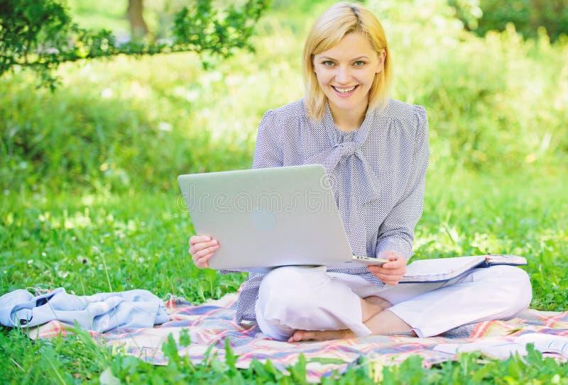 有膝上型计算机的妇女坐地毯草草甸 网上自由职业者的事业概念 开始自由职业者的事业的指南 宜人 免版税库存图片