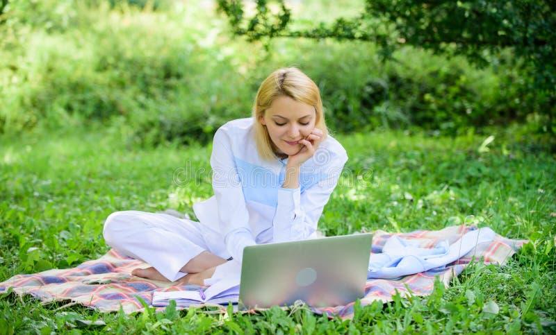 有膝上型计算机的妇女或笔记本坐地毯绿草草甸 企业夫人户外自由职业者工作 网上事务 免版税图库摄影