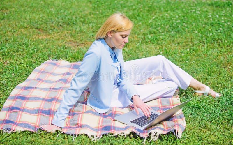 有膝上型计算机的妇女或笔记本坐地毯绿草草甸 开始做自由职业者的事务的步 37企业夫人 免版税库存照片