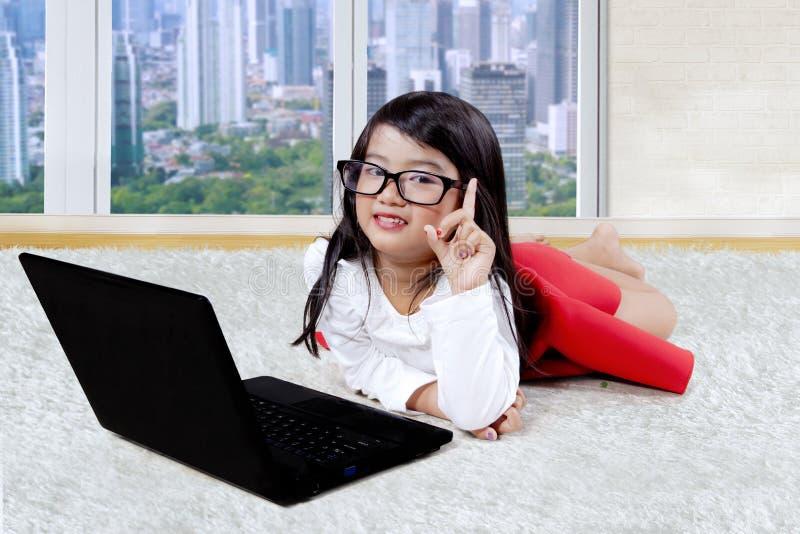 有膝上型计算机的孩子认为在地毯的想法 库存照片