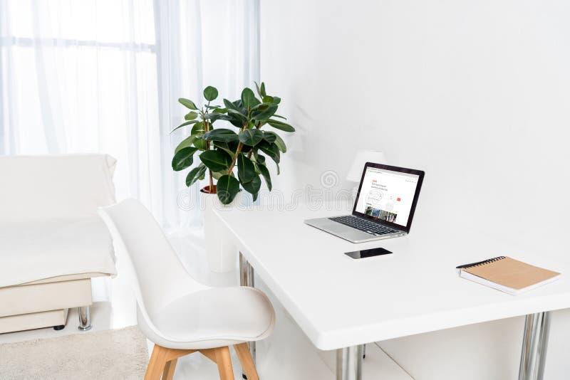 有膝上型计算机的家庭办公室有airbnb商标、智能手机和笔记本的 免版税库存照片