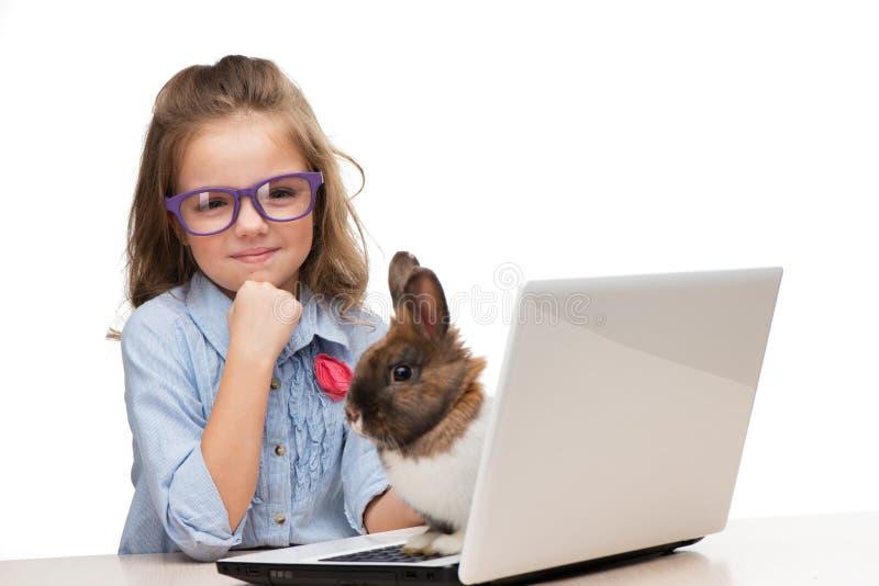 有膝上型计算机的对此的女孩和兔宝宝 免版税库存图片