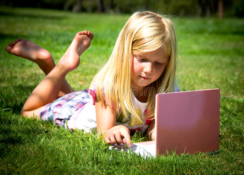 有膝上型计算机的小女孩 免版税库存图片