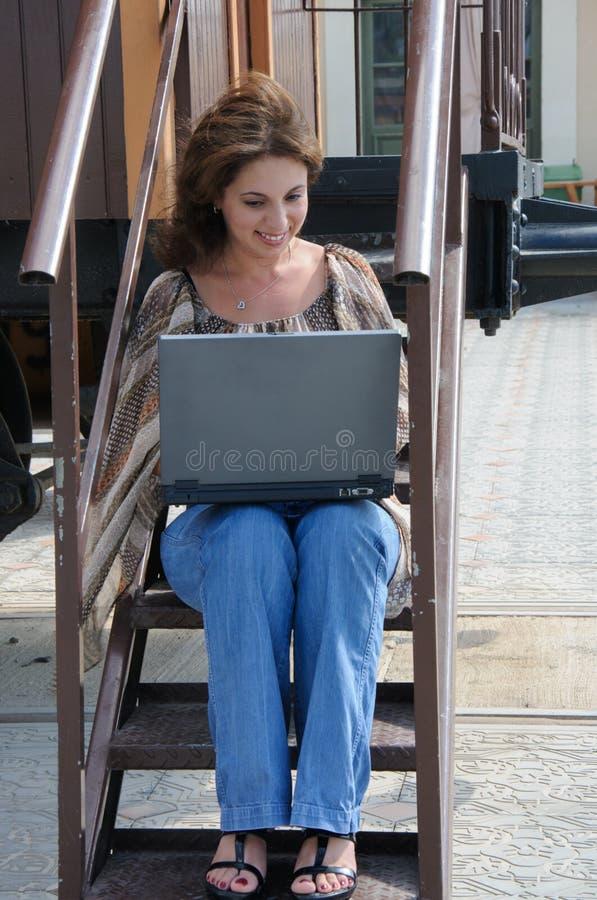 有膝上型计算机的少妇在步老火车 库存图片