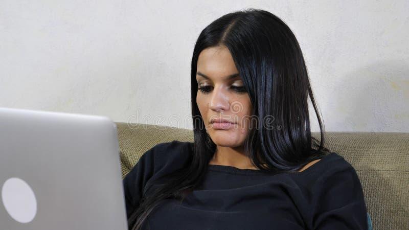 有膝上型计算机的少妇在运转在她起始的事务的长沙发 库存照片