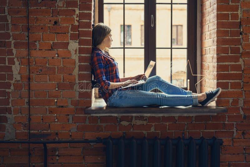 有膝上型计算机的少妇在顶楼 库存图片