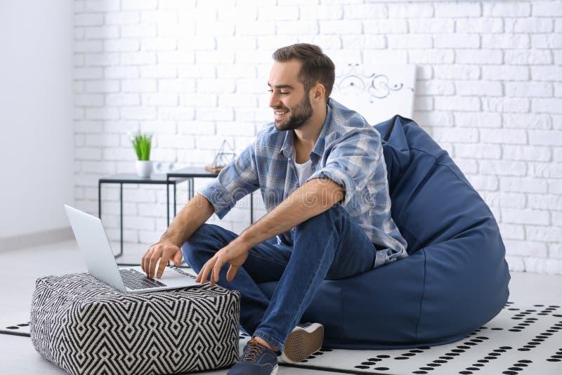 有膝上型计算机的年轻人在家坐装豆子小布袋椅子 库存图片