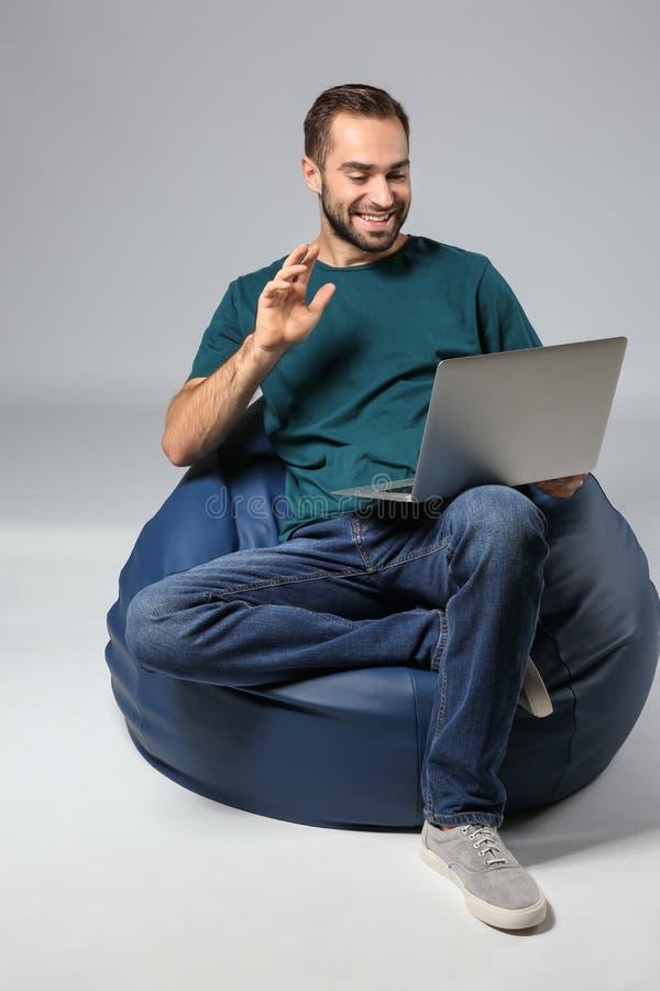 有膝上型计算机的年轻人坐装豆子小布袋椅子反对灰色背景 免版税库存图片