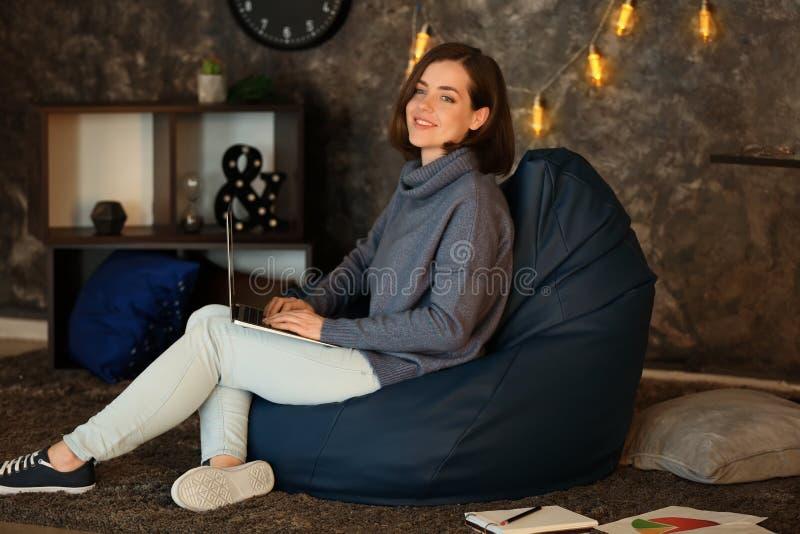 有膝上型计算机的年轻女人在家坐装豆子小布袋椅子 免版税图库摄影