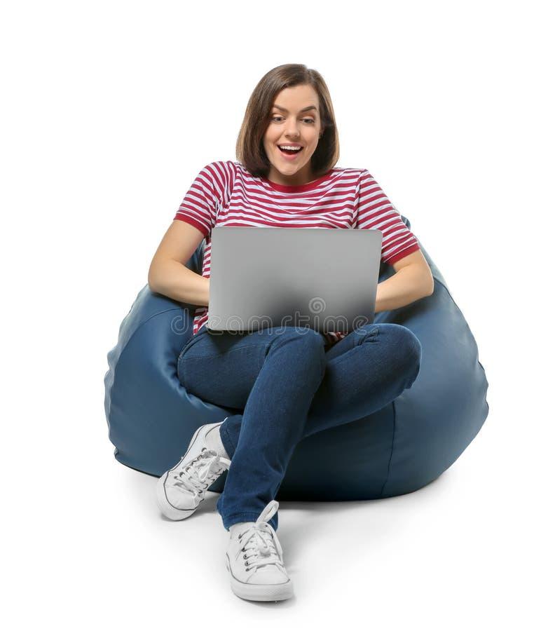 有膝上型计算机的年轻女人坐装豆子小布袋椅子反对白色背景 免版税库存图片