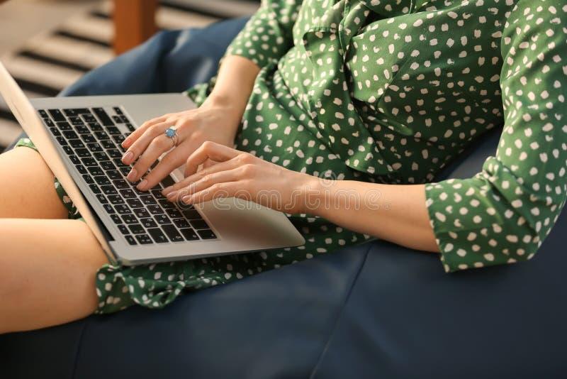 有膝上型计算机的年轻女人坐装豆子小布袋椅子,特写镜头 库存图片