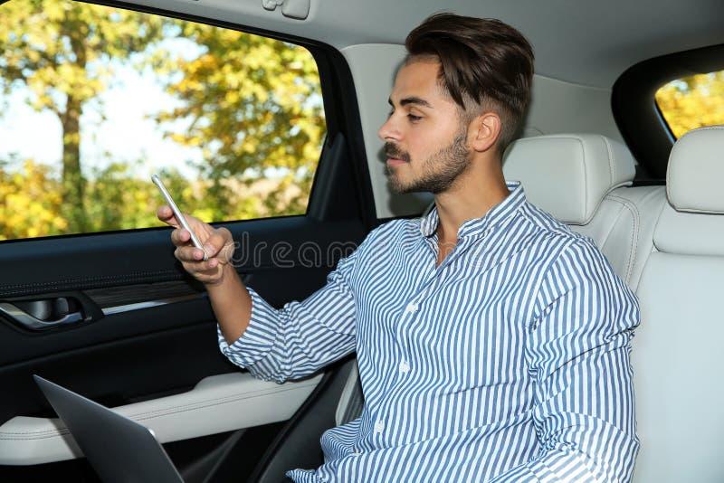 有膝上型计算机的年轻帅哥使用电话 免版税库存照片