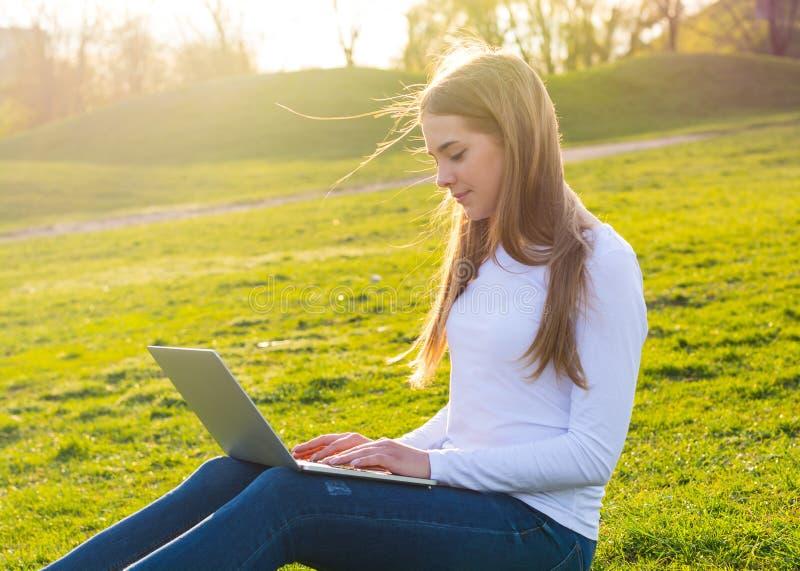 有膝上型计算机的年轻美丽的妇女坐草在夏天 库存图片