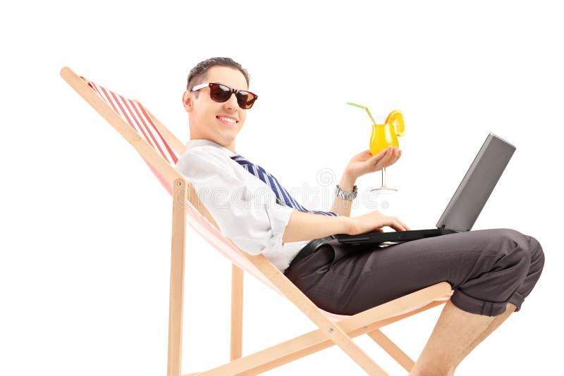 有膝上型计算机的微笑的大忙人坐海滩睡椅和holdin 免版税库存图片