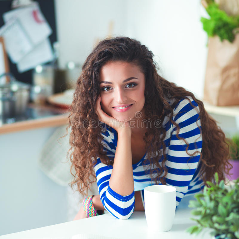 有膝上型计算机的微笑的少妇在厨房里在家 图库摄影