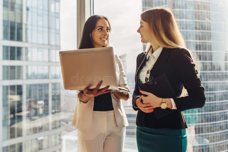 有膝上型计算机的微笑的少妇站立和谈话在办公室 库存照片