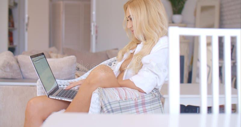 有膝上型计算机的性感的白肤金发的妇女坐椅子 库存照片