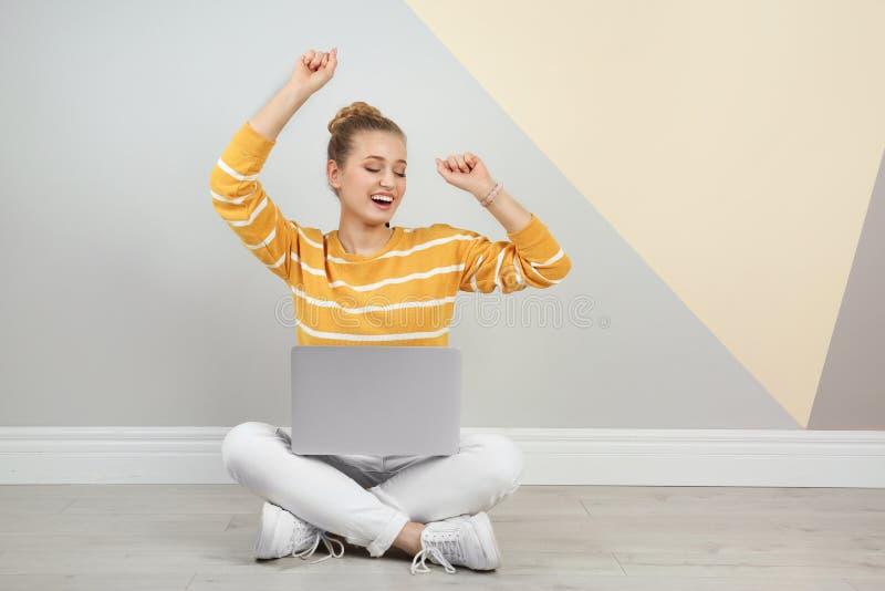 有膝上型计算机的情感年轻女人在颜色墙壁附近的地板上 免版税库存照片