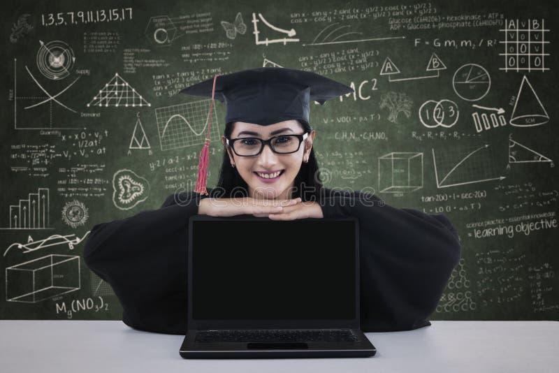 有膝上型计算机的愉快的女性毕业生 免版税库存图片