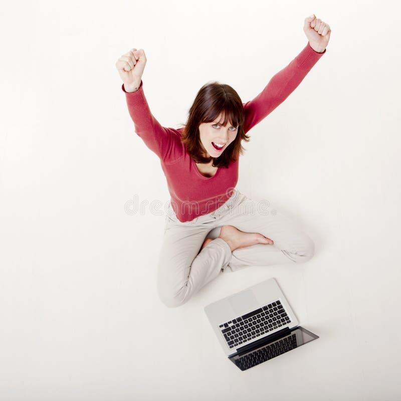 有膝上型计算机的愉快的妇女 免版税库存图片