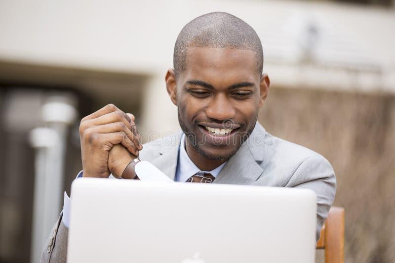 有膝上型计算机的愉快的微笑的商人 库存照片