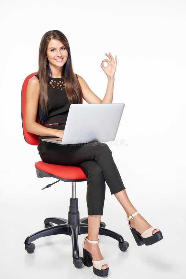 有膝上型计算机的打手势的女商人好 图库摄影