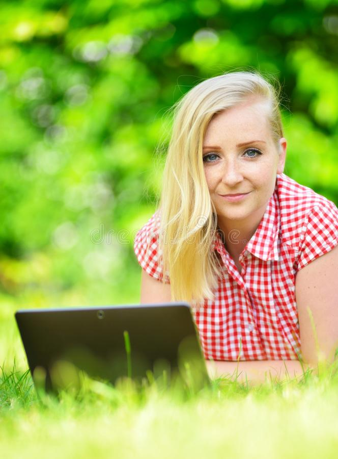 有膝上型计算机的新可爱的妇女 库存图片