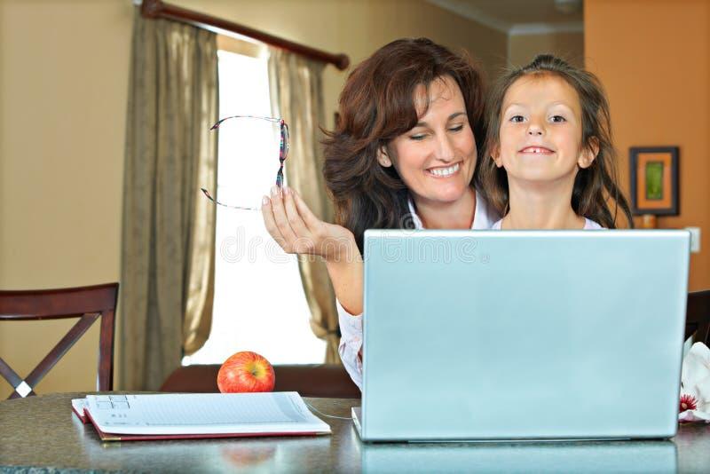 有膝上型计算机的母亲和女儿 库存照片