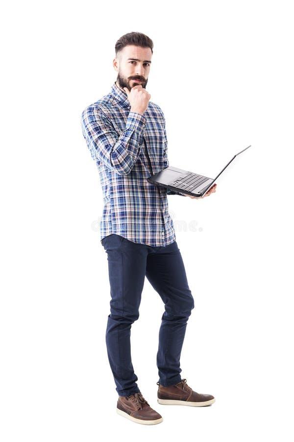 有膝上型计算机的沉思体贴的年轻有胡子的人认为和看照相机的 库存照片