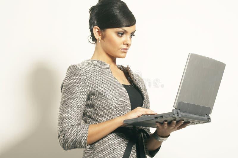 有膝上型计算机的深色的女商人 库存图片