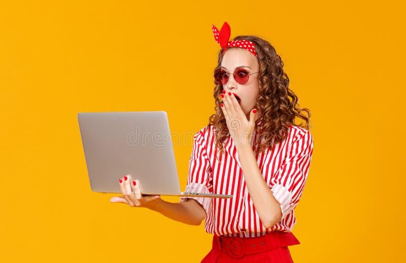有膝上型计算机的滑稽的快乐的妇女在黄色背景 免版税库存照片
