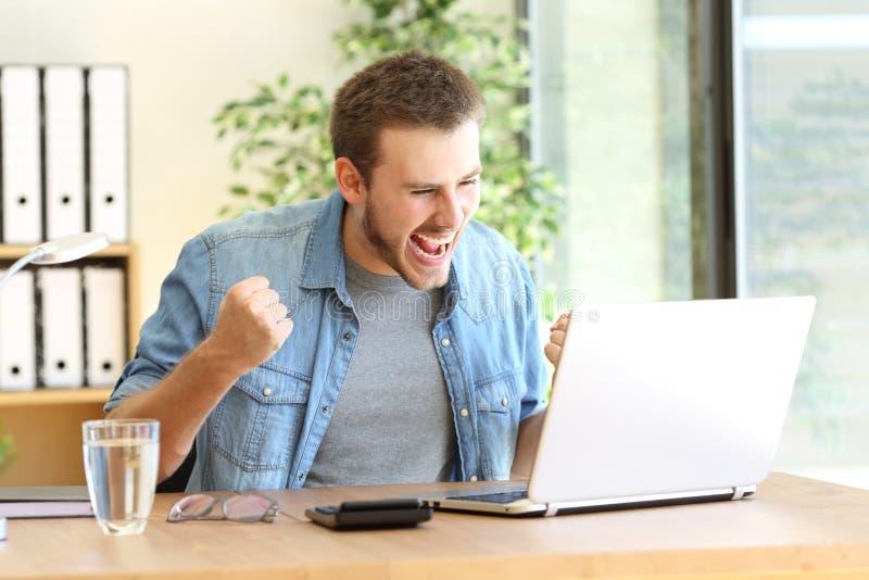 有膝上型计算机的激动的企业家在线 免版税库存照片