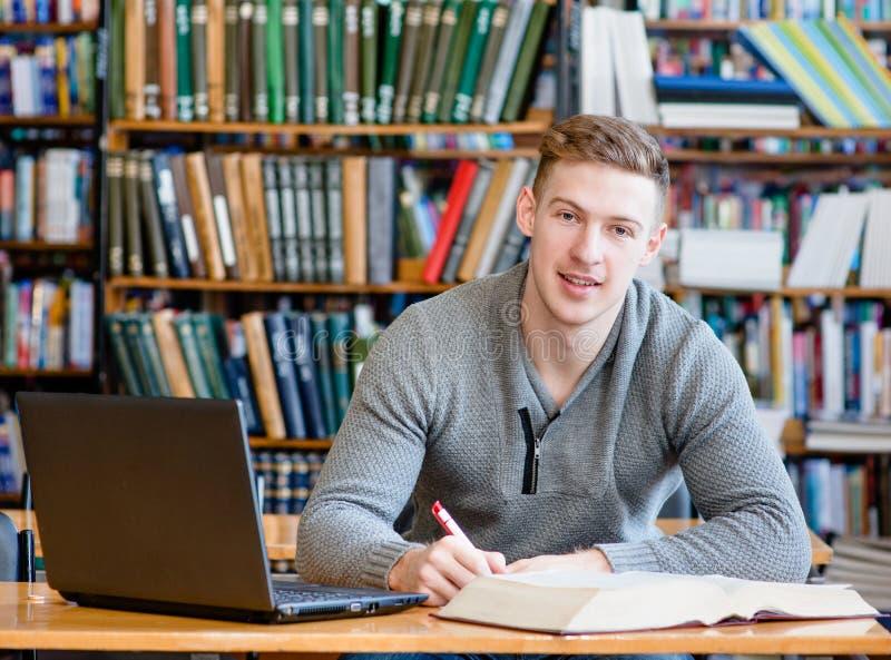 有膝上型计算机的男学生学习在大学图书馆里的 免版税库存图片