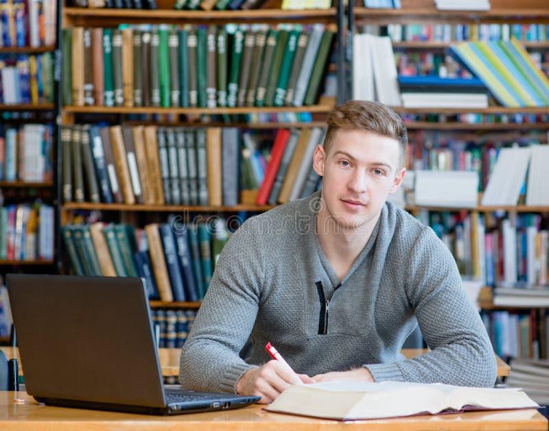 有膝上型计算机的男学生学习在大学图书馆里的 库存图片