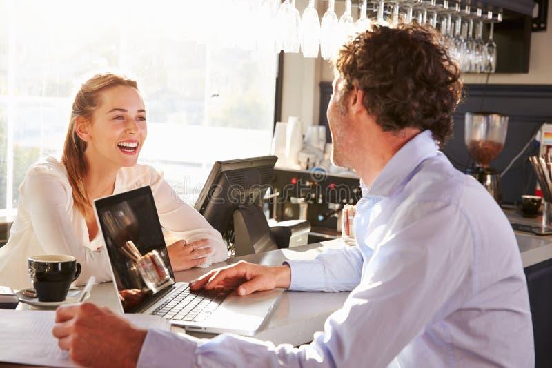 有膝上型计算机的男性餐馆经理谈话与女服务员 免版税库存图片