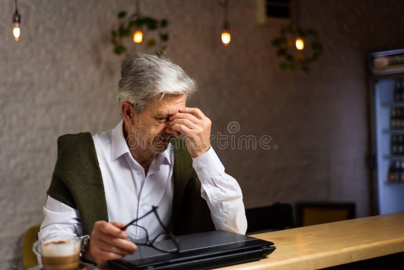 有膝上型计算机的疲乏的老人在酒吧 图库摄影