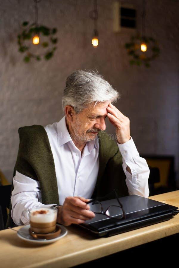有膝上型计算机的疲乏的老人在酒吧 免版税库存图片