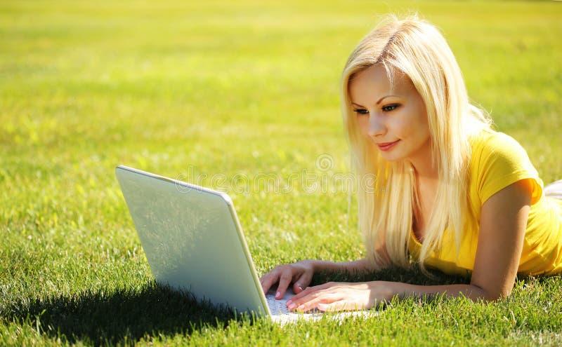 有膝上型计算机的白肤金发的女孩 绿色的微笑的美丽的妇女 图库摄影