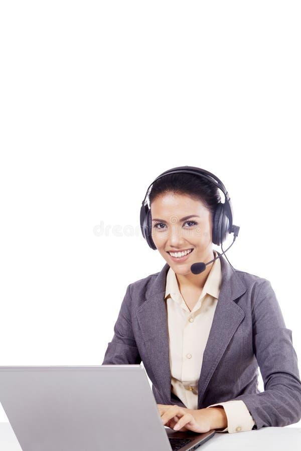有膝上型计算机的美丽的电话中心操作员在演播室 库存图片