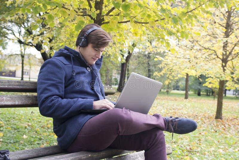 有膝上型计算机的年轻人在公园 库存照片