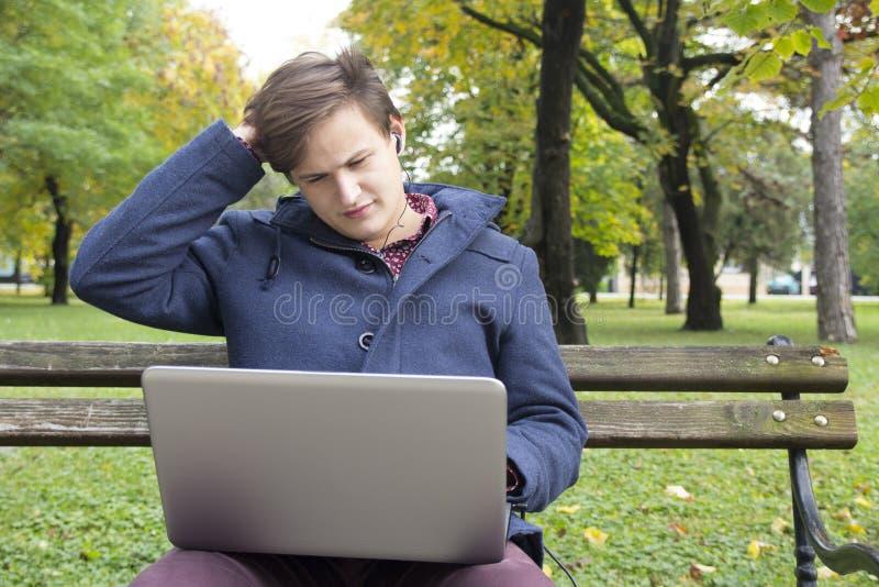 有膝上型计算机的年轻人在公园 库存图片