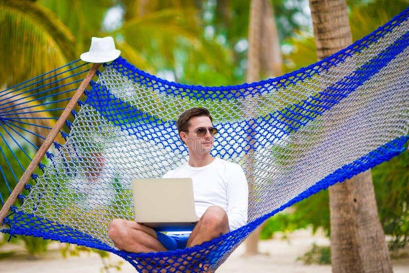 有膝上型计算机的年轻人在吊床热带假期 免版税图库摄影