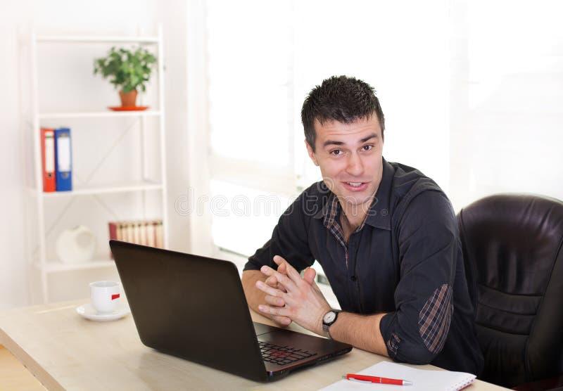 有膝上型计算机的滑稽的人在办公桌 免版税库存图片