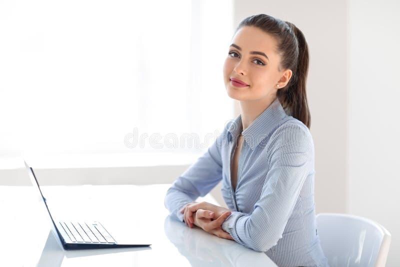 有膝上型计算机的年轻美丽的女商人在办公室 免版税库存照片