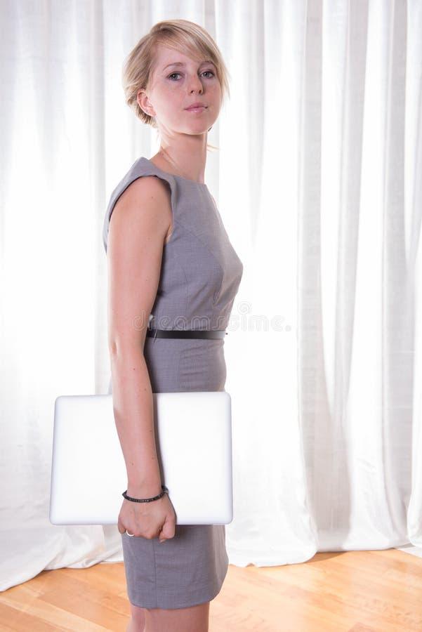有膝上型计算机的画象可爱的年轻女商人 免版税库存图片
